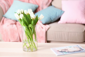 Wooden table with bouquet of tulips in living room