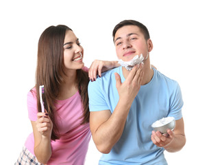 Young man shaving and his girlfriend cleaning teeth on white background