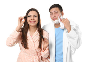 Young man with shaving foam and his girlfriend applying mascara on white background