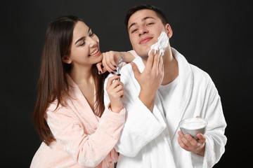 Young woman helping her boyfriend shaving on dark background