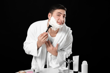 Young man shaving on dark background
