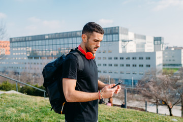 young man outdoor using smart phone hand hold - wifi technology, social network, internet concept
