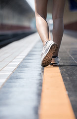 Close up shot woman legs wearing canvas shoes walking on yellow line