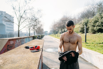 young man outdoor bare chested preparing for training - preparation, body confidence, sport concept