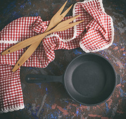 black cast-iron frying pan with a handle and two wooden forks