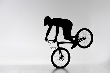silhouette of trial cyclist performing front wheel stand on white