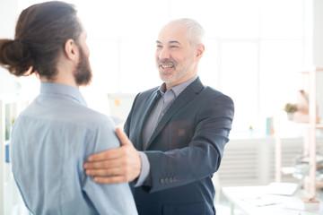 Mature executive congratulating his partner with good work