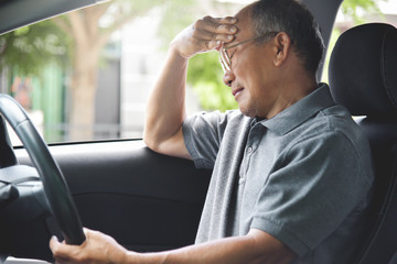 Asian Senior man having headache from migraine.