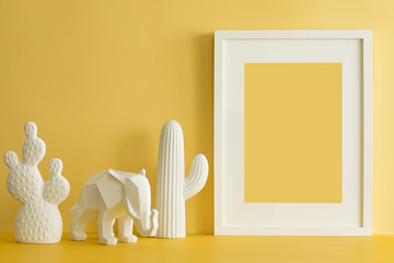 The design yellow desk with cacti, elephant and frame. Modern mock up concept.