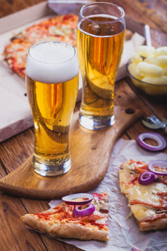 two glasses of beer with hot pizza on an old wooden table.