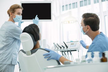 Best colleagues. Professional skilled dentists wearing uniforms and pointing at the screen