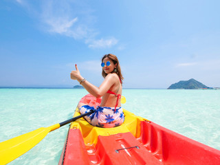 Asian woman on the kayak boat in Andaman blue sea and blue sky background location in Phuket island Thailand