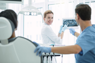 Good results. Pretty professional dentist talking with her colleague and showing teeth on the screen