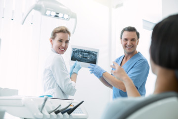 It is awesome. Inspired experienced dentists smiling and showing teeth on the screen to their patient
