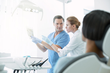 Discussing work. Professional experienced dentists discussing work and looking at the image of teeth