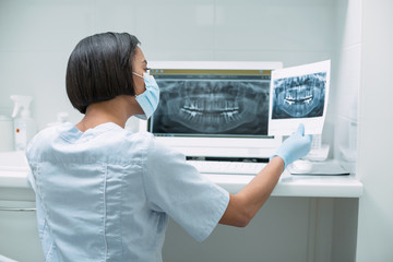 Analyzing results. Experienced dark-haired dentist holding an image and working on her advanced device
