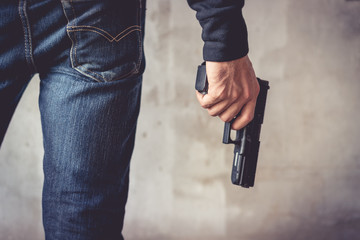 Close up of man holding hand gun. Man wearing blue jeans. Terrorist and Robber concept. Police and Soldier concept. Weapon theme