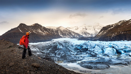 professional photographer with camera and tripod in winter. professional photographer looking to glacier in Iceland.