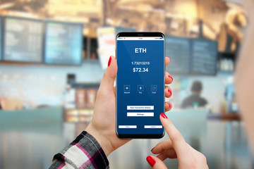Female paying bill in coffee shop with phone using Ethereum cryptocurrency. Blockchain shopping concept.