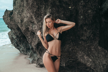 Blond girl with big breasts in a black swimsuit on a white sand beach. Portrait of a young woman with a beautiful body. Sexy model.