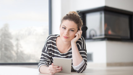 woman using tablet computer in front of fireplace