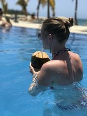 Femme en bikini dans la piscine buvant une noix de coco à la paille