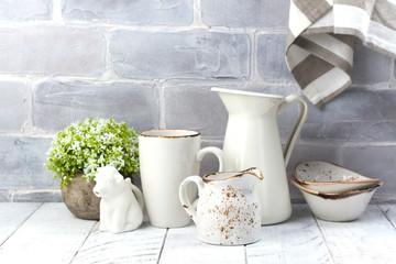 Ceramic and enamel crokery tableware agains brick wall