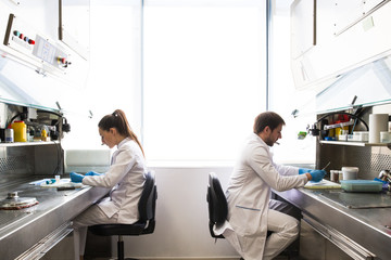 Side view of man and woman in lab coats sitting at tables and examining samples while working inresearch laboratory together.