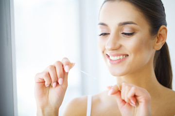 Teeth Care. Beautiful Smiling Woman Flossing Healthy White Teeth. High Resolution Image