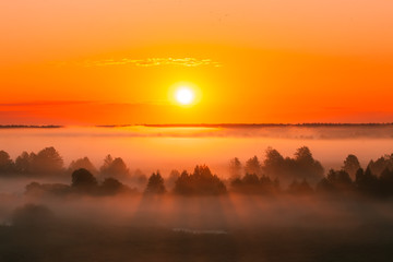 Amazing Sunrise Over Misty Landscape. Scenic View Of Foggy Morning Sky