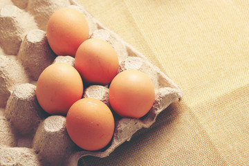 Fresh chicken eggs In the thirty box paper and have empty space for egg on cream fabric background.