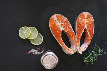 Close-up photo of fresh salmon fish with sea salt and lime slices on black table background.