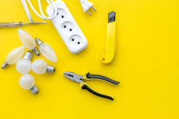 Electrical accessories at home. Bulbs, socket outlet, cabel on yellow background top view copy space