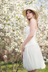 Young woman in the garden blooming in spring