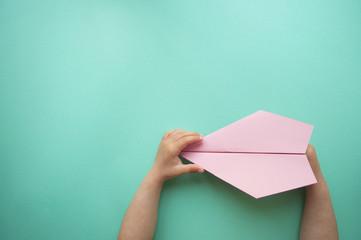 Paper plane in child's hands.
