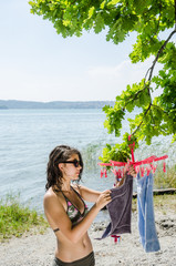 Attractive young woman in bikini hanging wet towels on a compact rotary clothes dryer at the shore of Lake Constance