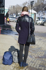 Young woman traveler with backpack and hat waiting for their train at train station travel concept.