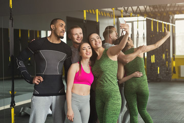 Young multiethnic group making selfie at gym