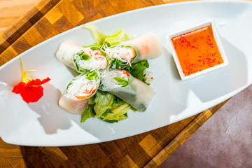 Vietnamese spring rolls with rice pasta on a plate with sauce and vegetables shot close-up