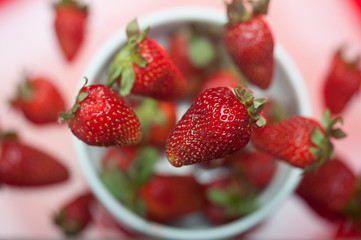 Fresh strawberries falling into a bowl top view with shallow depth of field