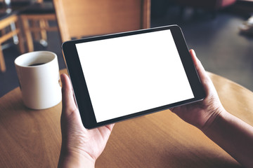 Mockup image of hands holding black tablet pc with blank white screen and coffee cup on table in cafe