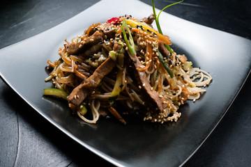 oriental cuisine restaurant food menu. noodle beef meat vegetable on a plate.