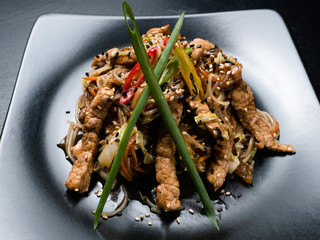 oriental cuisine restaurant food menu. noodle pork meat vegetable on a plate.