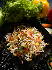 wheat sprouts and vegetable salad in a bowl on dark background. oriental cuisine food. traditional meal.