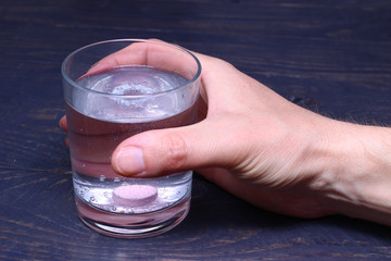 Glass pill with drugs in hand