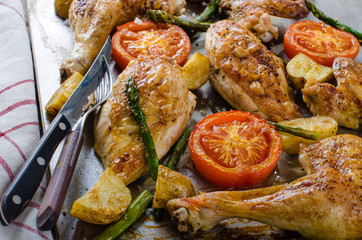 Oven-baked chicken with vegetables on the roasting tray