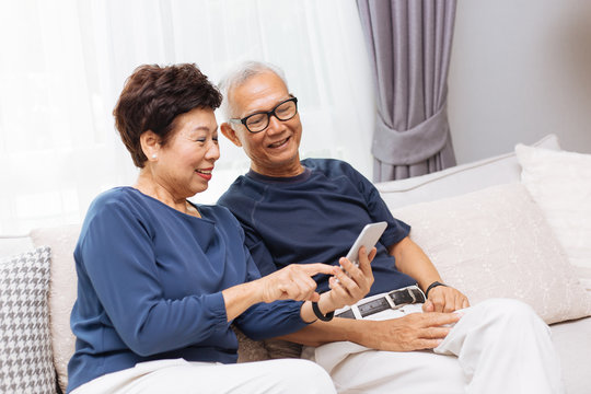 Senior Asian couple grandparents using a smart phone together on sofa at home