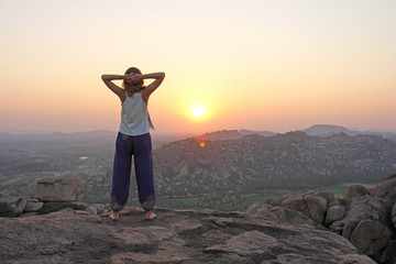 The girl at sunset. The girl stands with her back on the top of the mountain and looks at the sunset, welcomes the sun with her hands up, in Hampi. Meditation, alone with nature, silence. Hands up