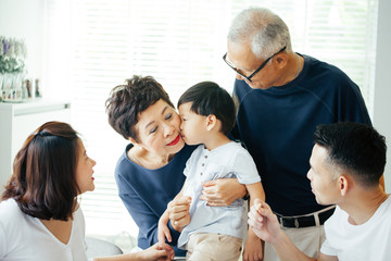 Boy kissing grandmother on cheeks with the whole Asian family of three generations together at home