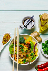 Chinese noodles with vegetables, mushrooms and meat in bowl on light blue wooden ruxtic table, top view